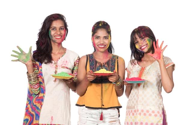 Счастливые молодые женщины веселятся с красочной пудрой на фестивале цветов холи
