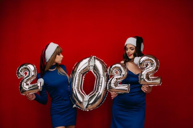 メリークリスマスと新年あけましておめでとうございますを祝うために銀の2022バルーンを保持している幸せな若い女性