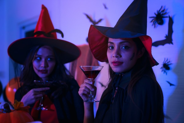 Счастливые молодые женщины в костюмах черной ведьмы на хэллоуин на вечеринке с тыквой и коктейлями