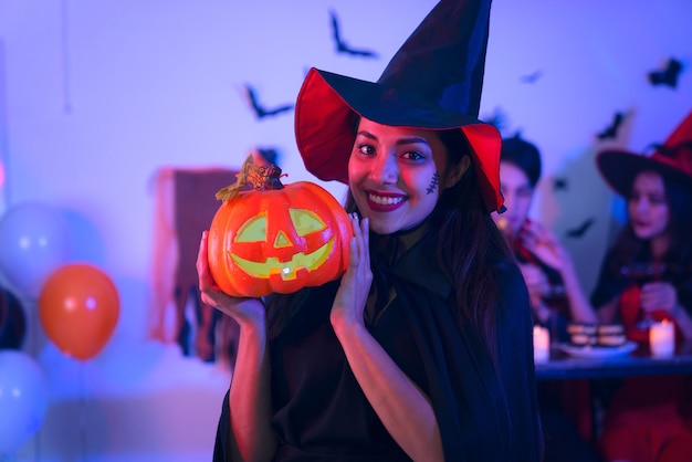 Счастливые молодые женщины в костюмах черной ведьмы на хэллоуин на вечеринке