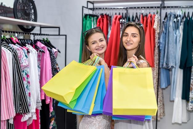 ショッピングバッグと衣料品店で幸せな若い女性 Premium写真