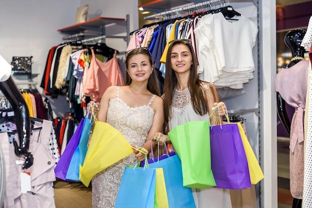 Счастливые молодые женщины в магазине одежды с хозяйственными сумками