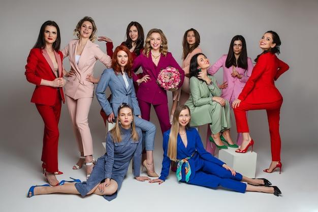 회색 배경에 고립 된 스튜디오에서 포즈 세련 되 고 밝은 옷에 행복 한 젊은 여성. 패션 컨셉