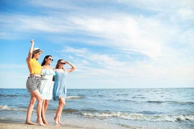 リゾートの海のビーチで幸せな若い女性