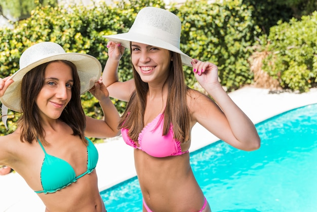 Happy young women posing in hats by pool