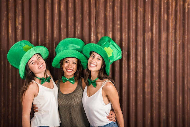 Happy young women in saint patricks hats embracing near wall