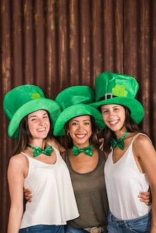 Happy young women in saint patricks hats hugging near wall