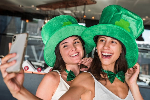 Happy young women in saint patricks hats taking selfie on smartphone
