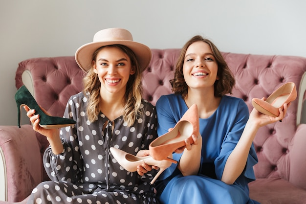 Happy young women shopaholics holding shoes.