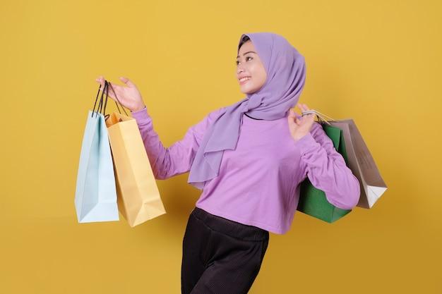 보라색 t 셔츠를 입고 가방을 보여주는 행복 한 젊은 여성 쇼핑 중독자