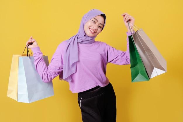 Happy young women shopaholics showing bags, wearing purple t shirt