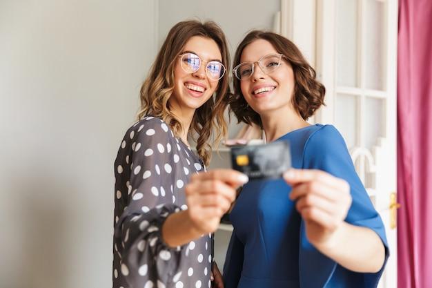 Happy young women shopaholics showing credit card.