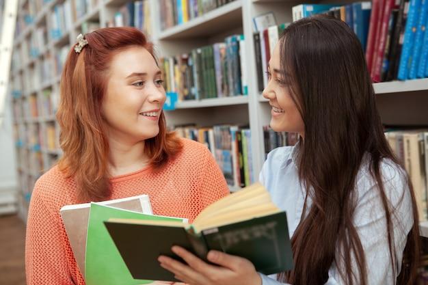 図書館で本を読みながらお互いに笑って幸せな若い女性