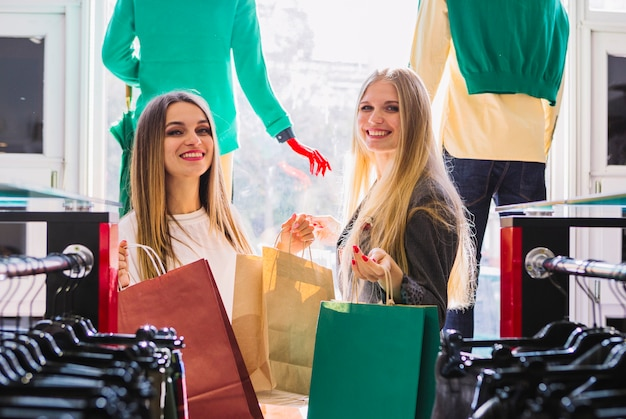 Happy young women standing in the clothing store holding shopping bags