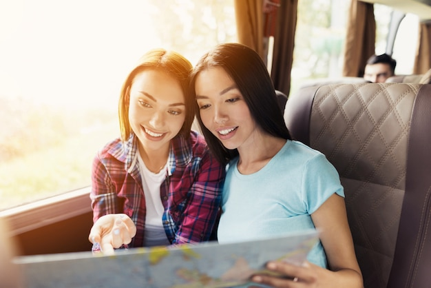 Happy young women study a map in travel bus.