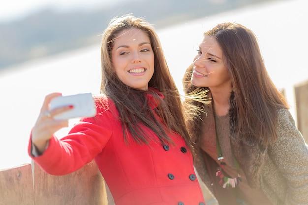 携帯電話で写真を撮る幸せな若い女性