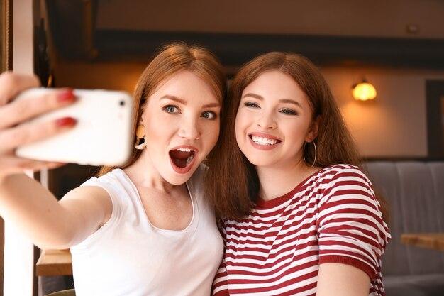カフェで自撮りをする幸せな若い女性