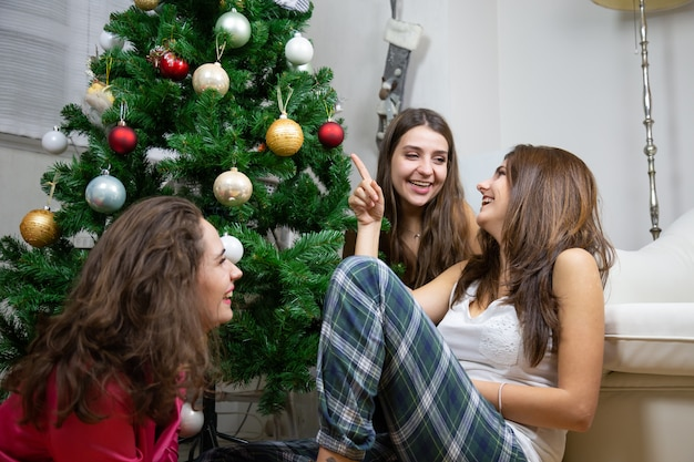 Happy young women talking sitting on the floor near the christmas tree
