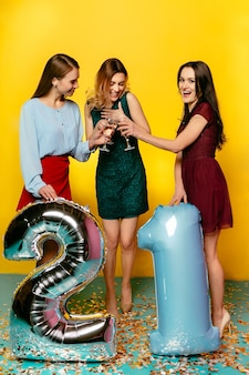 Happy young women toasting with champagne, holding balloon in form of twenty one