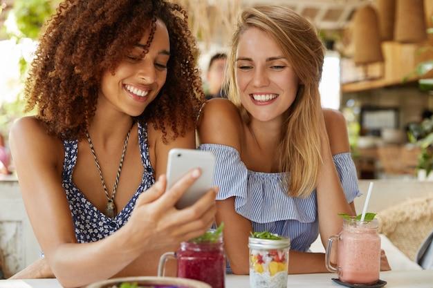 Giovani donne felici guardano video divertenti in internet su smart phone, si siedono insieme contro l'interno del bar, mangiano gustosi dessert e cocktail freschi. persone, relazioni e concetto di tecnologia moderna.