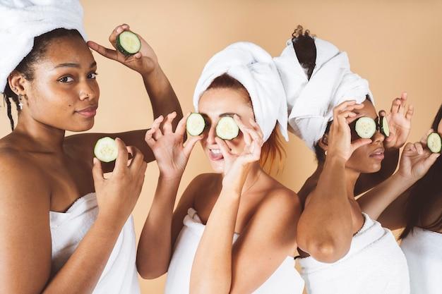 幸せな若い女性は頭に白いバスローブを着て、一緒に笑っている目に小さじ1杯のスキンケアマスクを作ります、