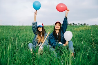 Happy young women with colored balloons in air sitting in field