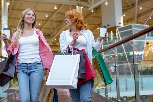 買い物を楽しんでいる買い物袋を持つ幸せな若い女性、女の子は彼らの購入を楽しんでいます。消費者とライフスタイルのコンセプト