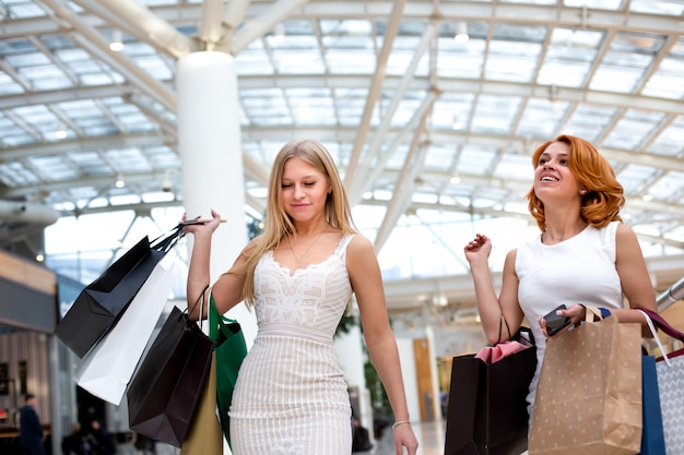 Happy young women with shopping bags enjoying in shopping, girls are having fun with their purchases. consumerism and lifestyle concept