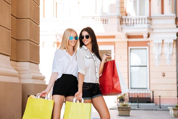 街の通りを歩いて買い物袋を持つ幸せな若い女性