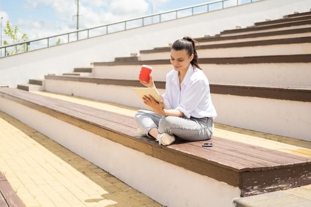 Счастливые молодые женщины с планшетом, держащим кофейный бумажный стаканчик, наслаждаясь солнечным днем, сидя в амфитеатре
