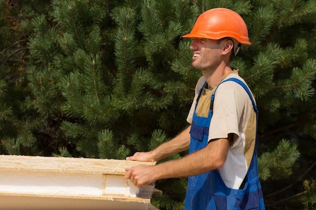 웃는 얼굴로 나무 벽 단열 패널을 들고 건물 부지에 있는 행복한 젊은 노동자, 카피스페이스가 있는 녹지에 대한 측면 전망