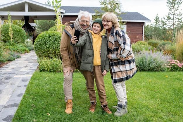 Счастливый мальчик в повседневной одежде и его ласковые бабушка и дедушка с улыбкой смотрят в камеру смартфона, делая селфи