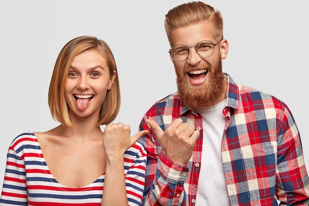 幸せな若者たちは一緒に楽しんで、楽しい表情でお互いを指さします。面白いかわいい女性は舌、市松模様のシャツで大喜びのひげを生やした男性のヒップスター、白い壁に隔離