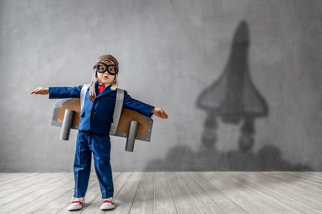Счастливый ребенок хочет стать летчиком. забавный малыш мечтает стать космонавтом.