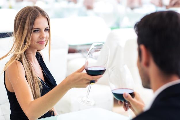 레스토랑에서 남자 친구와 함께 레드 와인을 마시는 hapyp 여자