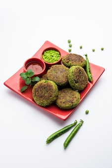 Хара бхара кабаб или кебаб - это рецепт индийской вегетарианской закуски, который подается с чатни из зеленой мяты на мрачной поверхности. выборочный фокус
