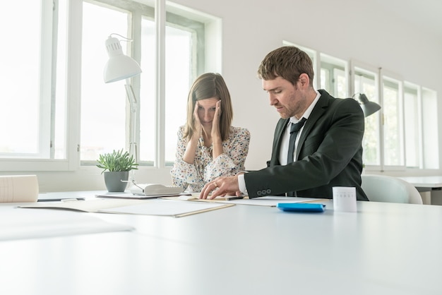 Harassed businesswoman checking the accounts with her male business partner as they sit at a table in the office using a manual adding machine in a low angle view with copy space.