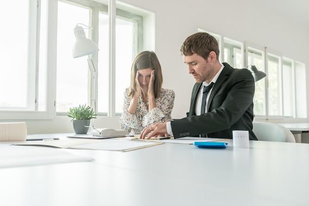 괴롭힘을 당하는 여성 사업가는 복사 공간이 있는 낮은 각도의 보기에서 수동 추가 기계를 사용하여 사무실의 테이블에 앉아 있을 때 그녀의 남성 비즈니스 파트너와 계정을 확인합니다.