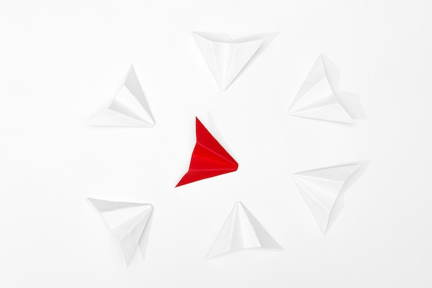 Harassment concept. red paper airplane is surrounded by white ones