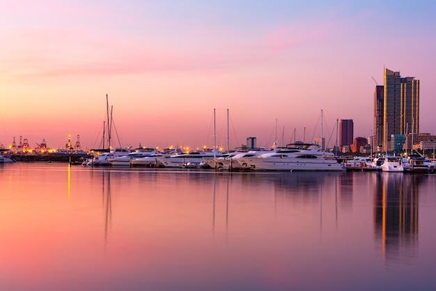요트로 가득한 항구와 일몰 동안 포착된 잔잔한 바다