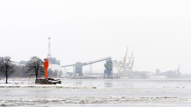 寒くて霧の冬の朝、リガ、ラトビアの灯台とコンテナクレーンのある港の風景
