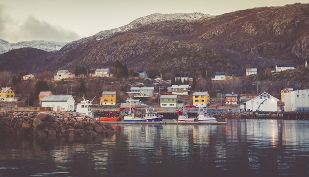 Harbor in a little fisherman village with moored boats and yachts with snow-capped peaks in the background.
