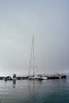 Гавань пришвартованные лодки парусник высокий туман утро