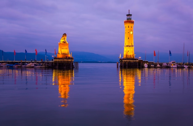 Вход в гавань на боденском озере. вид на старый маяк и статую льва у входа в порт в линдау на закате