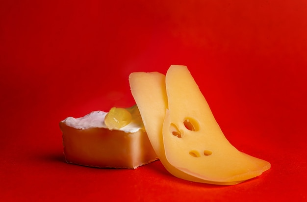 Твердый и мягкий сыр с белой плесенью на красном фоне