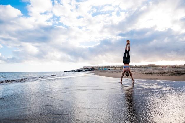 海岸のビーチで強くスポーティな女性のためのハード バランスの取れたポジション