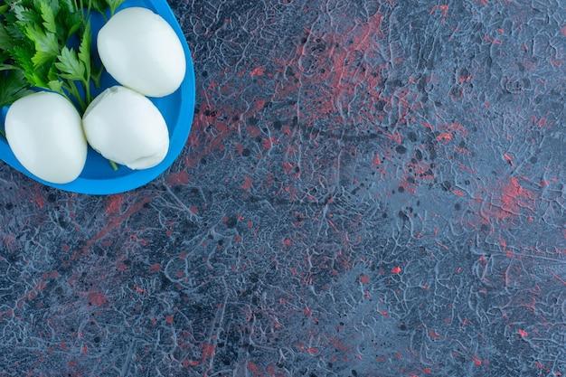 大理石の背景にハーブと固ゆで卵。