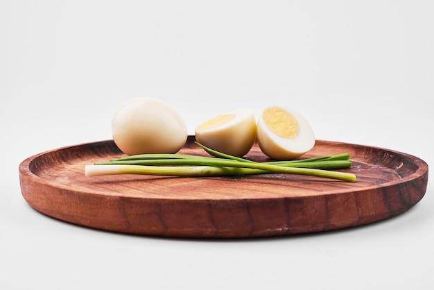 Uova sode e cipolla verde sul piatto di legno.