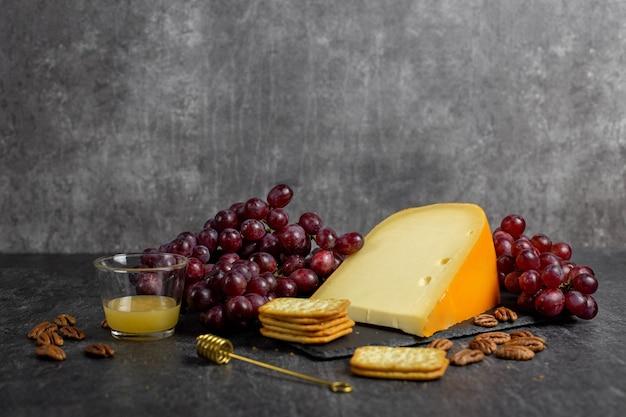 ダークグレーのコンクリート表面にブドウ、ピーカンナッツ、蜂蜜、クラッカーを添えたハードチーズゴーダ