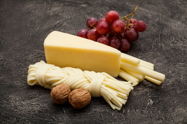 Hard cheese and pigtail, decorated with walnuts and grapes